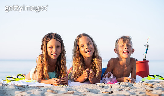 Three cute kids lying at the beach - gettyimageskorea