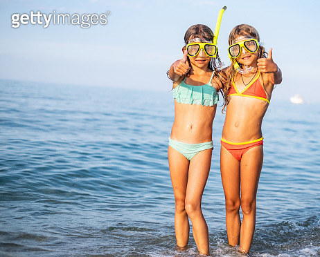 Two sisters standing at the sea coast and looking at camera - gettyimageskorea