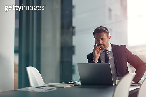 Shot of a businessman working on a laptop in an office - gettyimageskorea