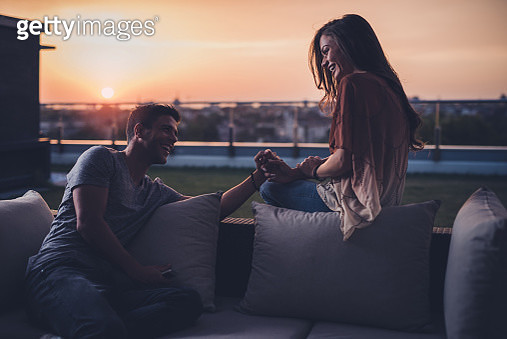 Happy couple holding hands while talking on a penthouse terrace at sunrise. - gettyimageskorea