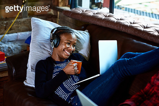 Attractive woman reclining on sofa and smiling, watching movie on computer, communication, online chat - gettyimageskorea