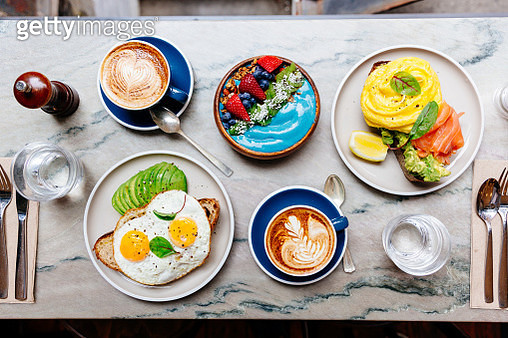 Brunch at cafe with avocado toast, fried and scrambled egg, salmon, smoothie bowl and coffee - gettyimageskorea