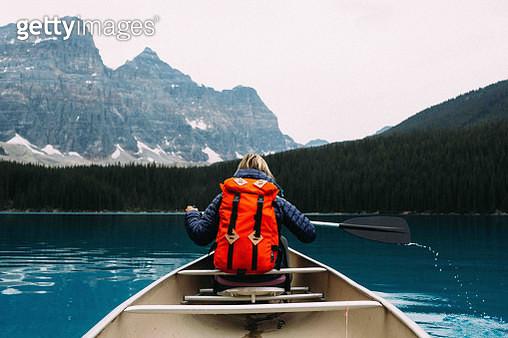Rear view of mid adult woman paddling canoe, Moraine lake, Banff National Park, Alberta Canada - gettyimageskorea