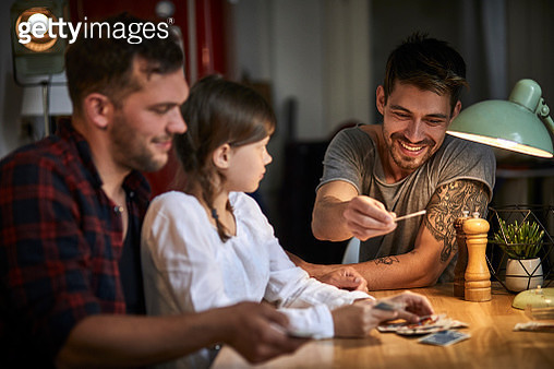 Two men playing cards with girl at table at home - gettyimageskorea