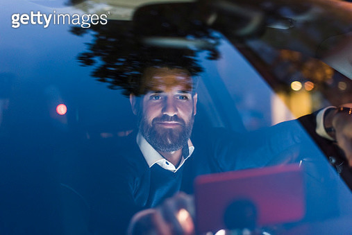 Businessman using navigation device in car at night - gettyimageskorea