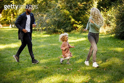 Family running for fun with daughter in park area - gettyimageskorea