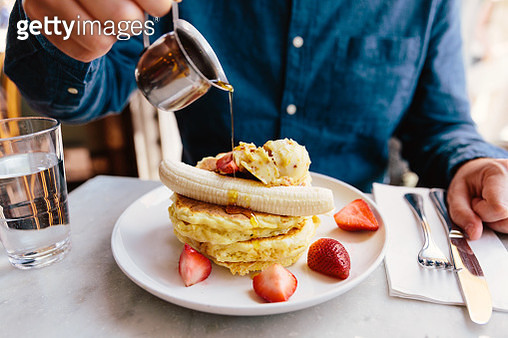 Man pouring maple syrup on pancakes with banana and strawberry - gettyimageskorea