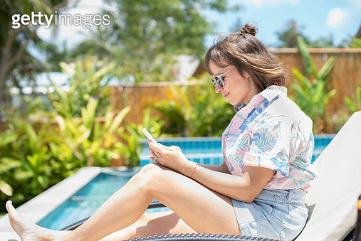 Woman using smart phone on sunny poolside lounge chair - gettyimageskorea