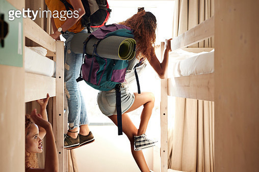 Young women arriving to room with bunk beds, at youth hostel - gettyimageskorea