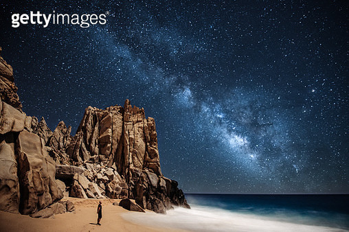 Lone person stargazing by the ocean in Cabo San Lucas - gettyimageskorea