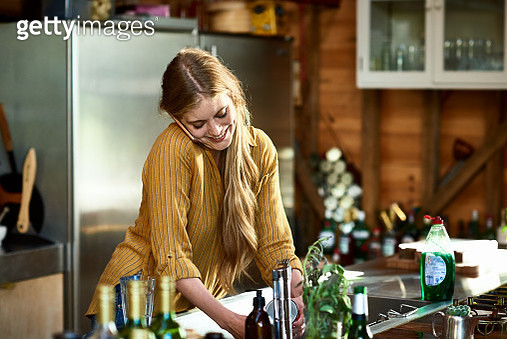 Woman washing up in kitchen and smiling, head cocked to one side cradling phone on shoulder - gettyimageskorea
