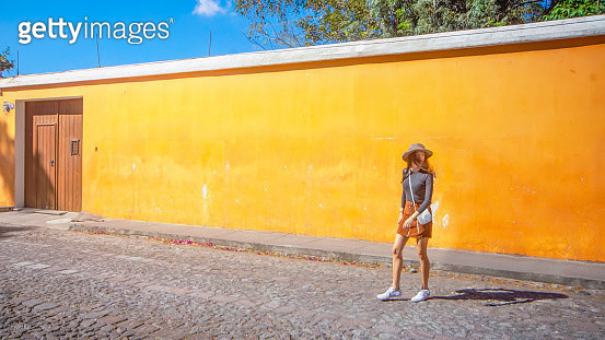 Beautiful girl wearing hat and short skirt walking at the cobblestone streets of Antigua, Guatemala. Antigua are today a favorite tourist destination. Antigua is as a partially restored colonial city with majestic churches and monasteries and cobblestone  - gettyimageskorea