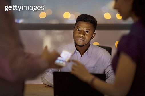 Man watching office colleagues discuss plans - gettyimageskorea