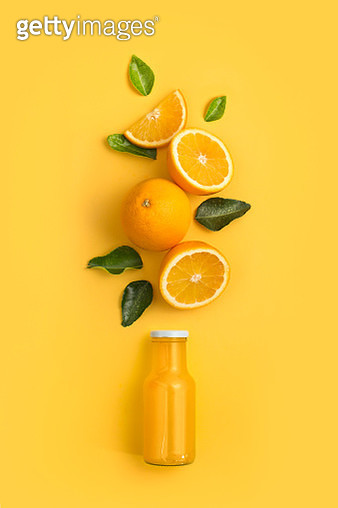 Orange fruits bursting out from a juice bottle. Yellow background. - gettyimageskorea