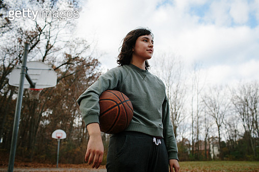 Young woman holding basketball in outdoor court - gettyimageskorea