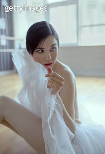 Woman in ballet dress sitting on the studio floor - gettyimageskorea