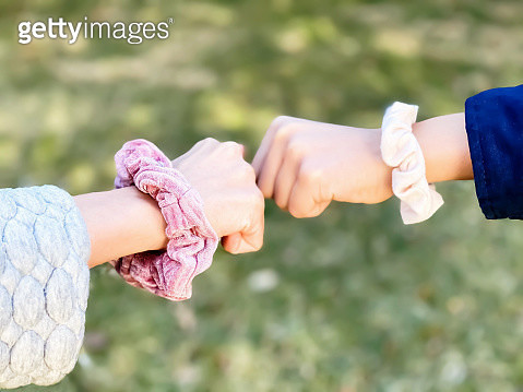 fist bump greeting between two mixed-race teen girls with hair scrunchies on wrists - gettyimageskorea