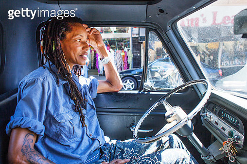 African American woman with dreadlocks and tattoos driving her classic car - gettyimageskorea