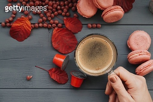 Cropped Image Of Woman Holding Coffee Cup By Raw Coffee Beans And Macaroons On Table - gettyimageskorea