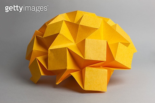 Studio shot of yellow paper folded into an abstract organic form - gettyimageskorea