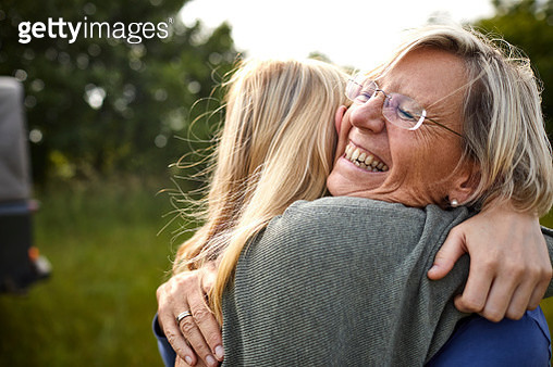Happy senior woman and young woman hugging outdoors with a jeep in background - gettyimageskorea