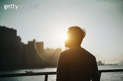 Silhouette of young man standing against urban cityscape and harbour looking up to sky in deep thought - gettyimageskorea