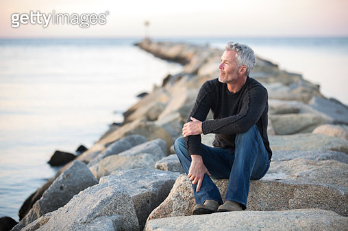Gray-haired man contemplating on coastal rocks at dusk, Dennis, Massachusetts, USA - gettyimageskorea