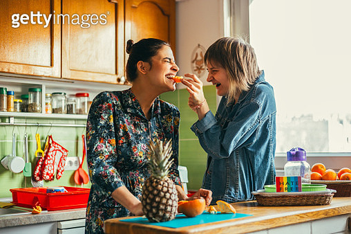 Two females hug at the kitchen - gettyimageskorea