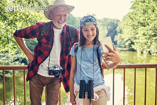granddaughter taking a selfie with her grandfather while taking a break from hiking - gettyimageskorea