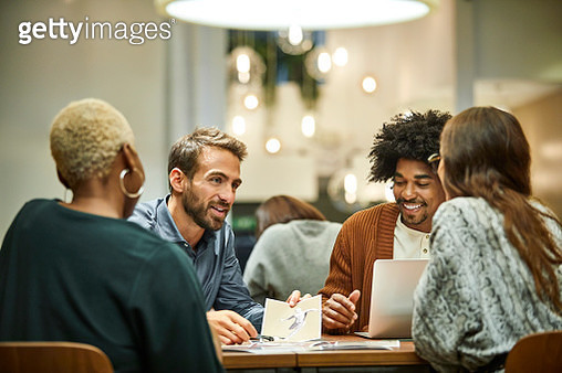 Multi-ethnic business professionals discussing at desk. Male and female coworkers are working in office. They are in meeting. - gettyimageskorea