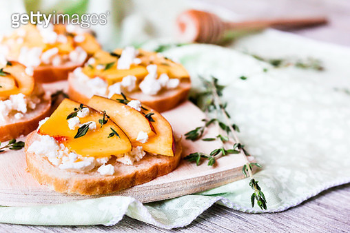 Homemade Bruschetta with nectarines, salted feta cheese, dried thyme and honey on a wooden board, selective focus - gettyimageskorea