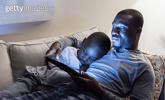 Father and son lying on sofa using digital tablet - gettyimageskorea