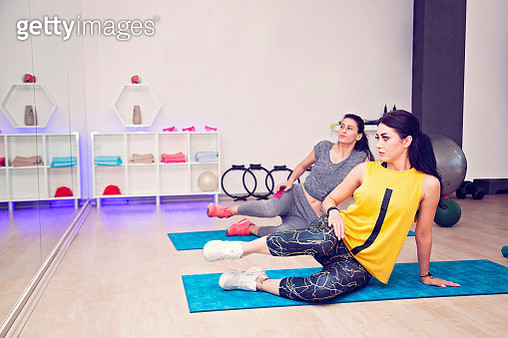 Two young women in gym doing exercises on mat - gettyimageskorea