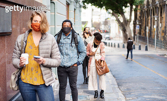Group of diverse people in face masks social distancing on a city sidewalk - gettyimageskorea