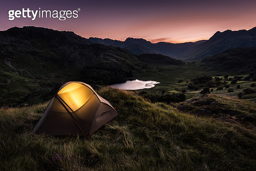 Tent lit up by torch inside, sitting on a ledge overlooking the Langdale Valley and Blea Tarn in the English Lake District - gettyimageskorea