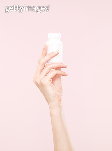 female hand, white tub of tablets, medication, pink background - gettyimageskorea
