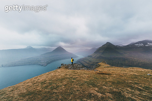 Woman in yellow raincoat  looking at scenic view of seaside on Faroe Islands - gettyimageskorea