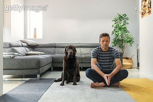 Man meditating with his pet dog - gettyimageskorea