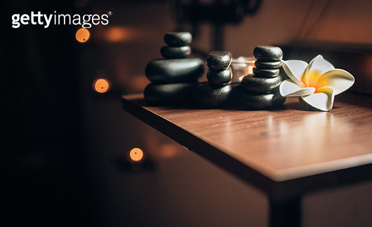 Lit candles and black massage stones in Zen spa - gettyimageskorea