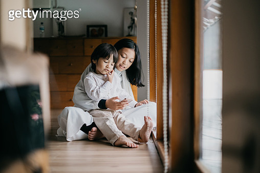 Brother and Sister Playing Mobile Phone Together - gettyimageskorea
