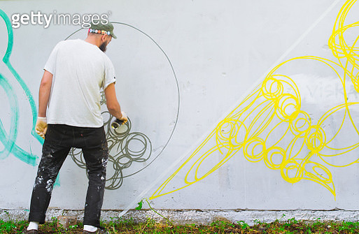Rear View Of Artist Spraying On Wall - gettyimageskorea