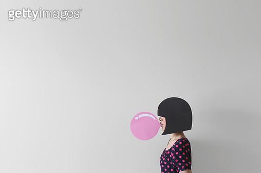Woman blowing a conceptual bubble gum bubble - gettyimageskorea