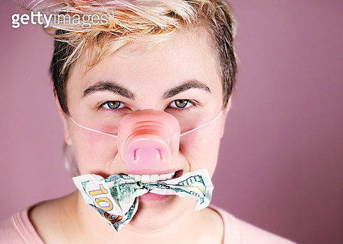 Feminine genderqueer young adult wearing a pink pig nose and holding hundred dollar bills in mouth (piggy bank concept) - gettyimageskorea