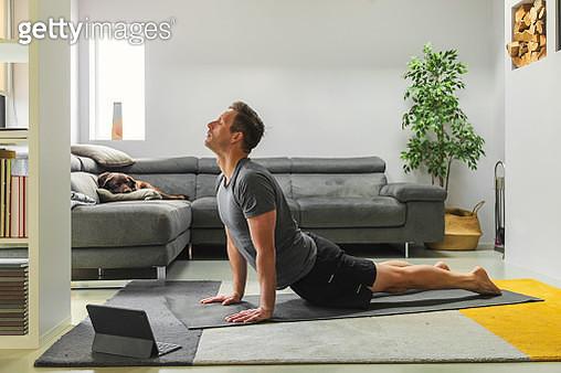 Man practising yoga at home - gettyimageskorea