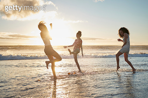 Three young women kicking water and laughing on the beach - gettyimageskorea