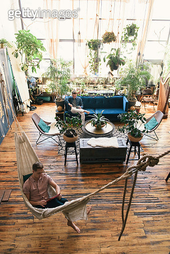 High angle view of gay man relaxing in hammock while boyfriend sitting on sofa at loft apartment - gettyimageskorea