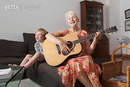 Playful boy sitting with grandmother singing while playing guitar on sofa at home - gettyimageskorea