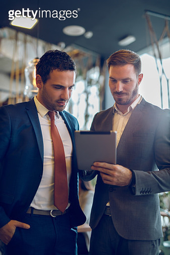Two young businessmen discussing business strategy using digital tablet - gettyimageskorea