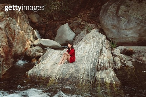 Woman Sitting On Rock Formation - gettyimageskorea