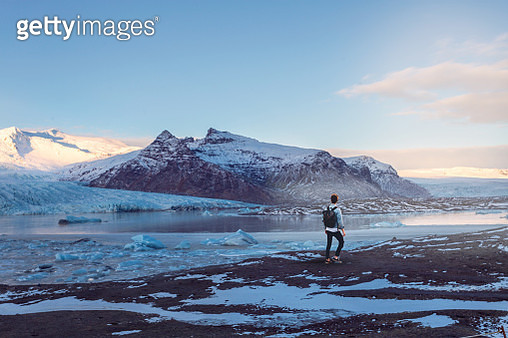 Rear View Of Man Standing By Lake Against Snowcapped Mountains - gettyimageskorea
